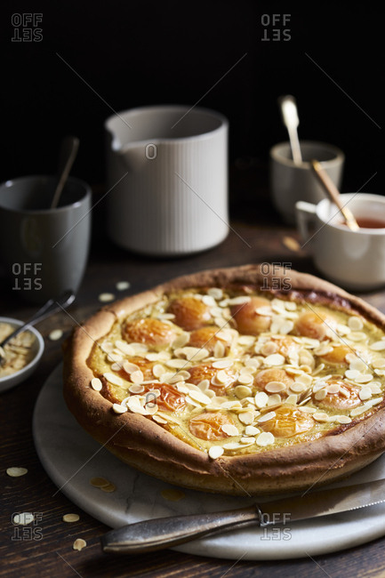 Apricot tart with custard, sweet yeast dough and sliced almonds on dark rustic table
