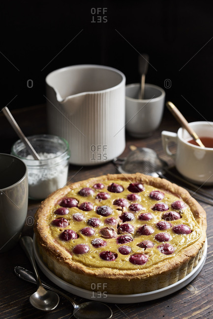 Red gooseberry tarte with custard and sweet yeast dough on dark rustic table