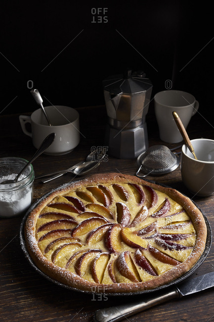 Peach tart with custard and sweet yeast dough on dark rustic table
