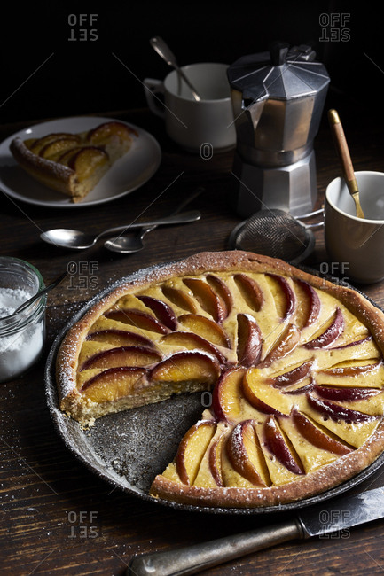 Homemade peach tart with custard and sweet yeast dough in dark rustic table setting