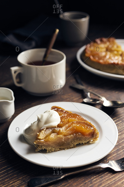 Cut slice of homemade apple tarte tatin with whole tart in the background