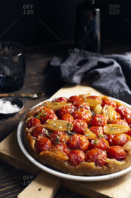 Tomato tarte tatin with  shallots and thyme served on dark wooden table