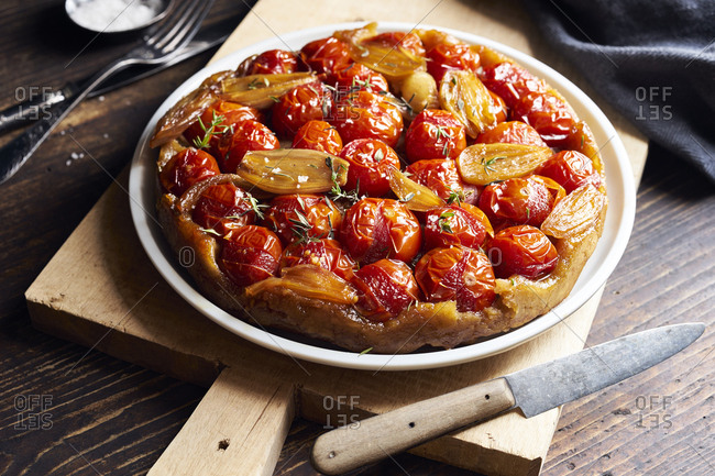 Tomato tarte tatin with  shallots and thyme on cutting board on rustic wooden table
