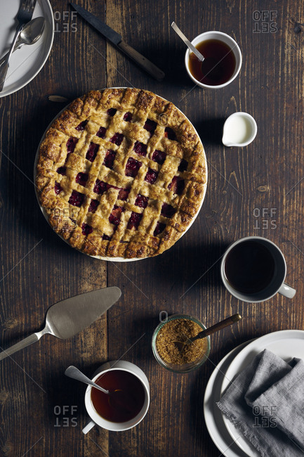 Overhead view of homemade nectarine and red currant pie on dark wooden surface