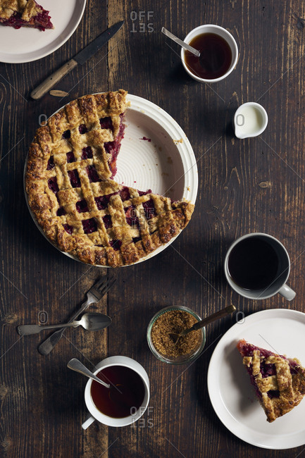 Overhead view of homemade nectarine and red currant pie on dark wooden table