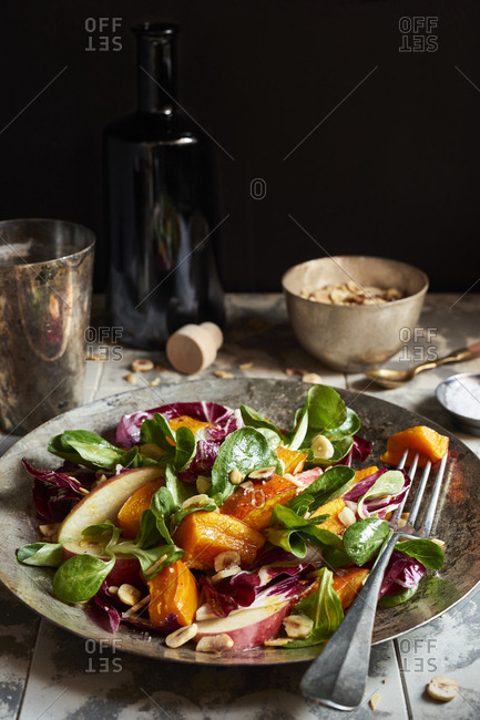 Colorful fall salad with roasted pumpkin, field salad, radicchio, apples and chopped hazelnuts on vintage silver plate