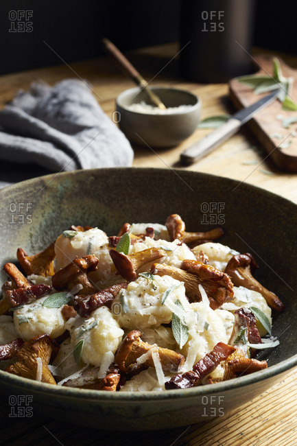 Gnocchi in creamy sauce with chanterelle mushrooms, pancetta and fresh sage on wooden table