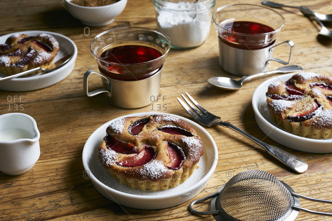 Honey and yogurt tartlets with plums  for tea on rustic wooden table