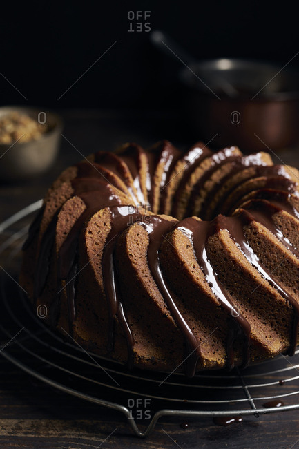 Garnishing homemade hazelnut bundt cake with chocolate ganache and chopped hazelnuts