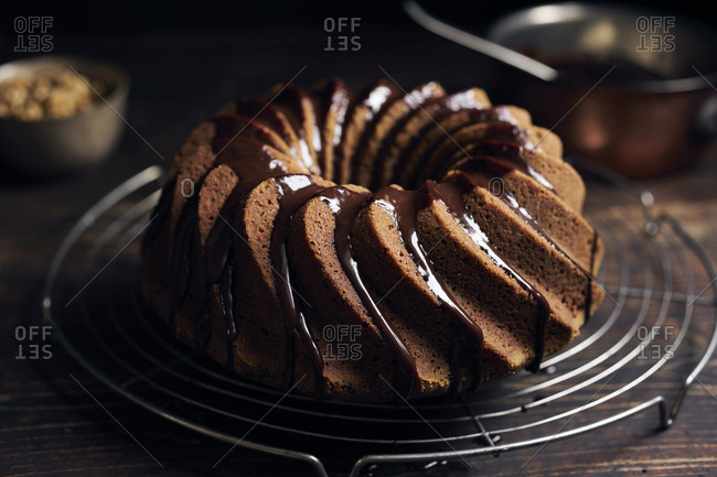 Garnishing hazelnut bundt cake with chocolate ganache and chopped hazelnuts