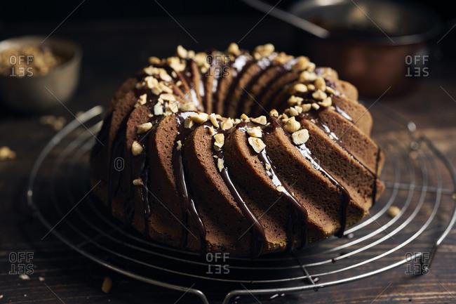 Hazelnut bundt cake garnished with chocolate ganache and chopped hazelnuts