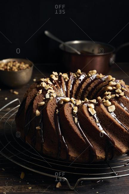 Homemade hazelnut bundt cake garnished with chocolate ganache and chopped hazelnuts