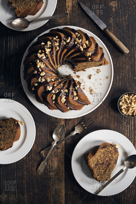 Hazelnut bundt cake with chocolate ganache and chopped hazelnuts, some slices cut and served