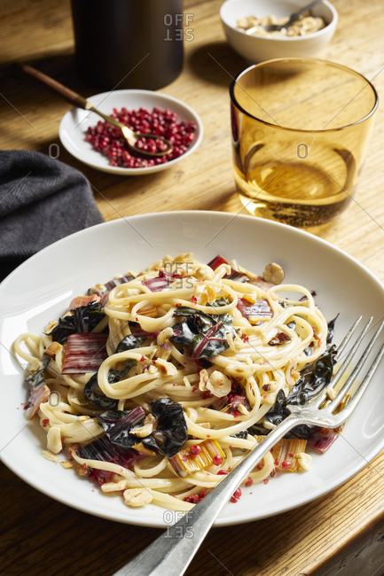 Linguine with swiss chard in creamy sauce with chopped hazelnuts and red pepper on rustic table