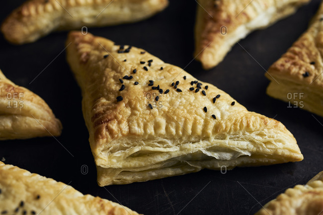 Homemade savory puff pastry triangles filled with spinach and feta cheese