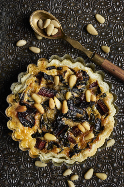 Puff pastry tartlet with swiss chard on vintage metal surface