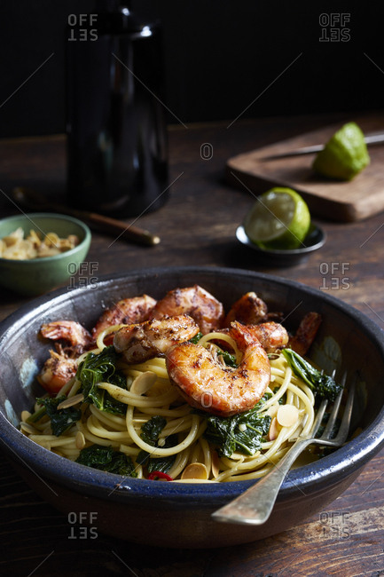 Spaghetti with kale and fried prawns on rustic wooden  table