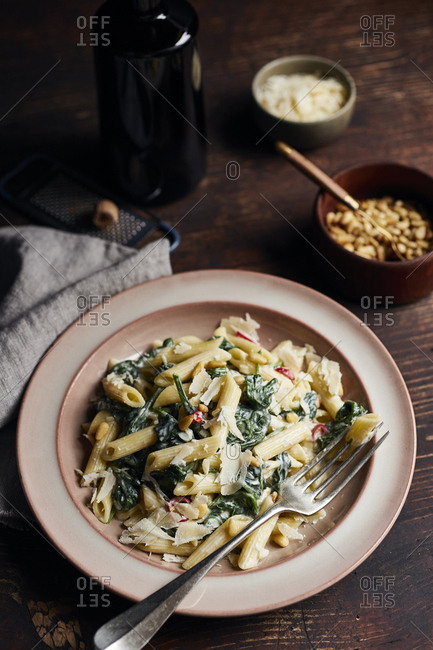 Penne with spinach in creamy sauce with blue cheese and red cillies on dark table
