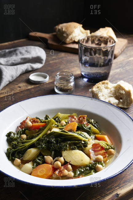 Winter vegetable stew with kale and fried bacon on dark wooden table