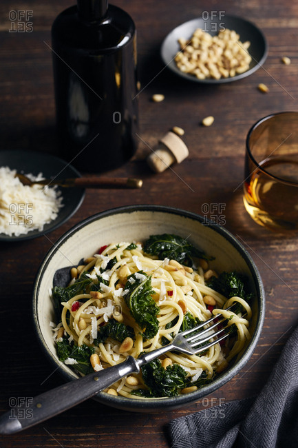 Spaghetti with kale, chilli and pine nuts on rustic wooden table