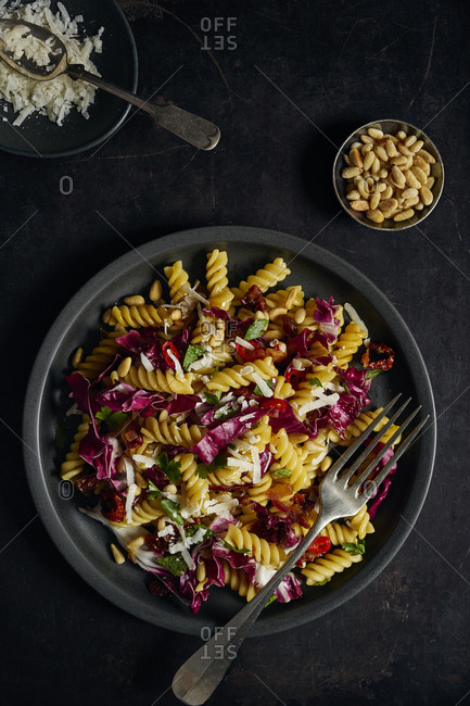 Saffron fusilli with radicchio, dried tomatoes, raisins and pine nuts on black background