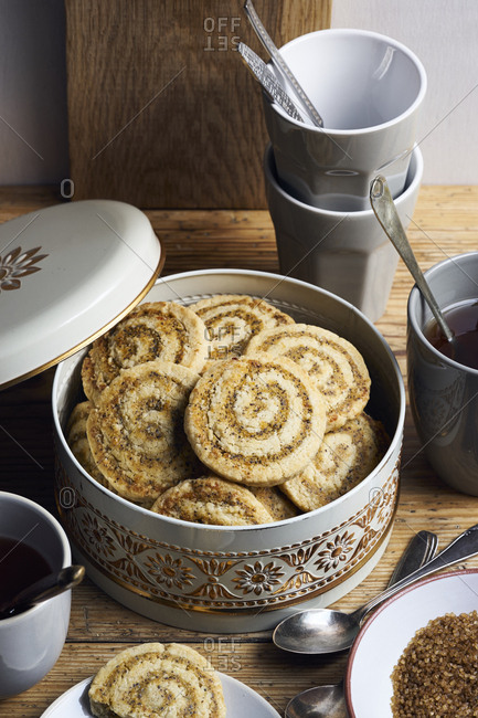 Shortcrust apricot marzipan rolls with poppy seeds in cookie tin on rustic wooden table
