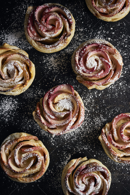 Homemade apple tarts in rose shape on black background sprinkled with powdered sugar