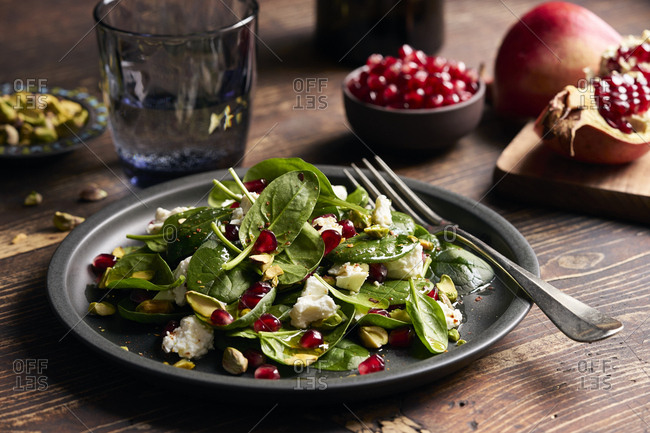 Fresh baby spinach salad with feta cheese, roasted pistachios and pomegranate seeds on dark wooden table