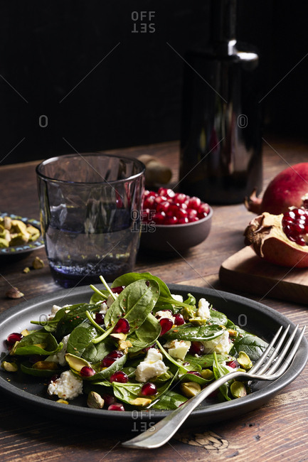 Fresh baby spinach salad with feta cheese, roasted pistachios and pomegranate seeds on rustic wooden table