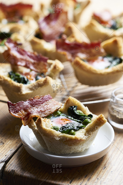 Egg muffins with spinach, peas and bacon in bread muffin cups