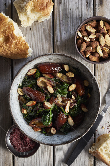 Bowl of spinach with dates, roasted almonds and sumac on rustic wooden table