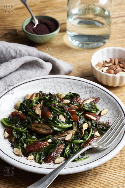 Spinach with dates, roasted almonds and sumac on wooden table