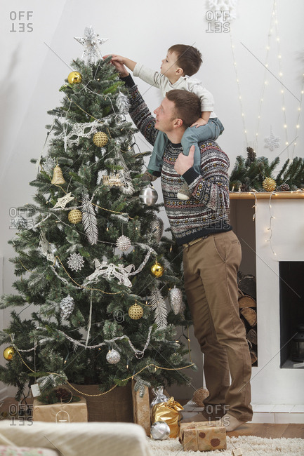 Full length of man carrying son shoulders while decorating Christmas Tree at home