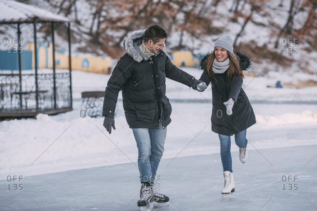 Full length of happy couple holding hands while enjoying ice-skating