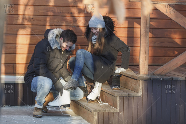 Man crouching while assisting happy woman in wearing ice skates on steps