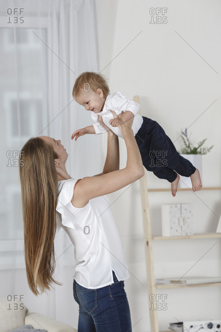 Happy mother holding daughter aloft at home