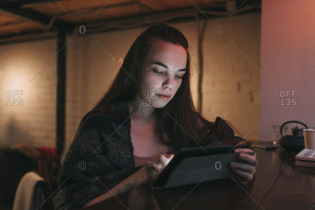 Beautiful young woman using digital tablet at cafe