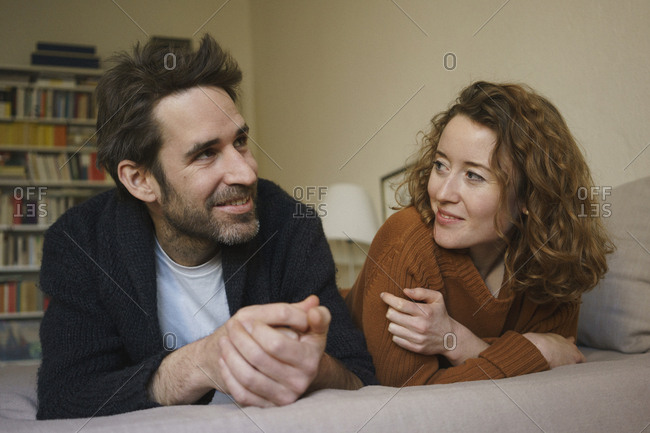 Happy mid adult couple lying on bed at home