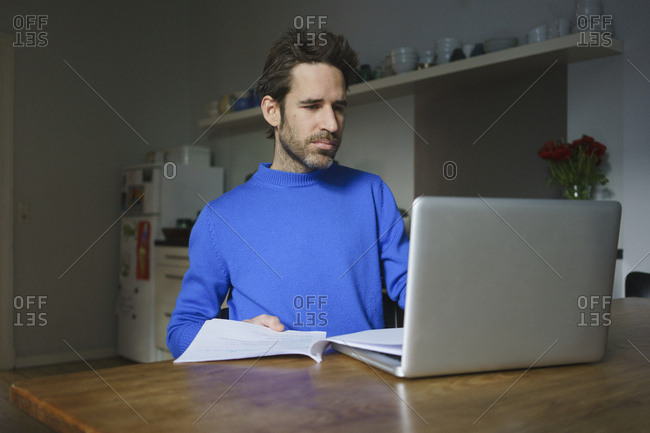 Worried mid adult man sitting with documents using laptop at table in kitchen