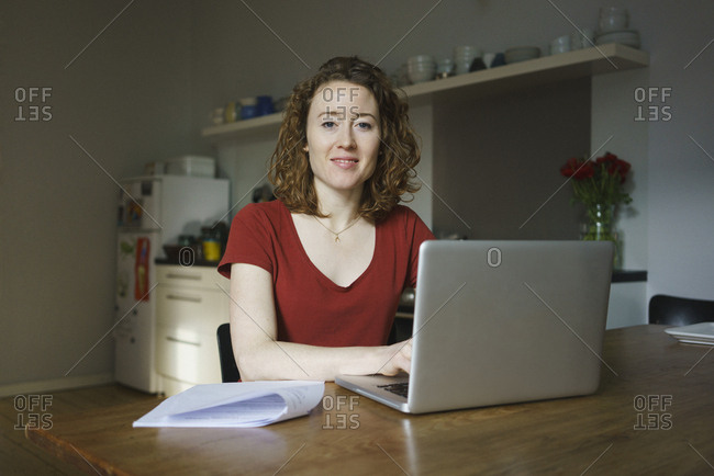 Portrait of confident woman sitting with laptop and documents at table in kitchen