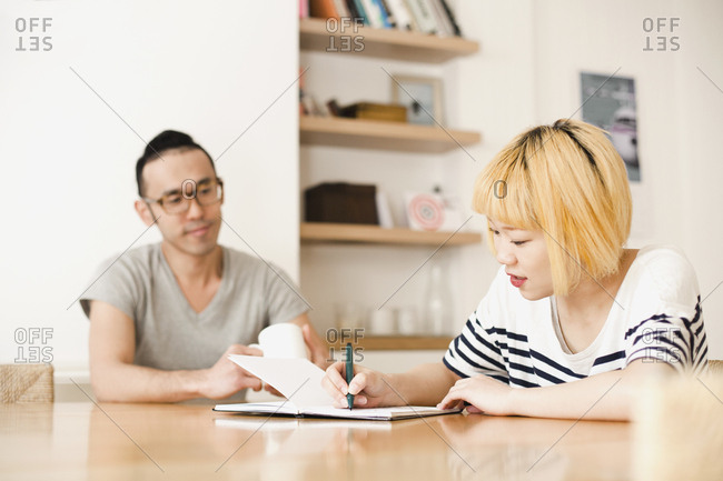 Young woman writing in diary by man at home