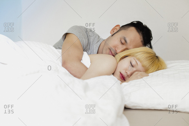 Young couple sleeping on bed against wall at home