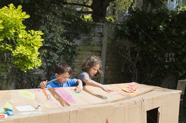 Multi-ethnic friends painting cardboard playhouse in back yard on sunny day