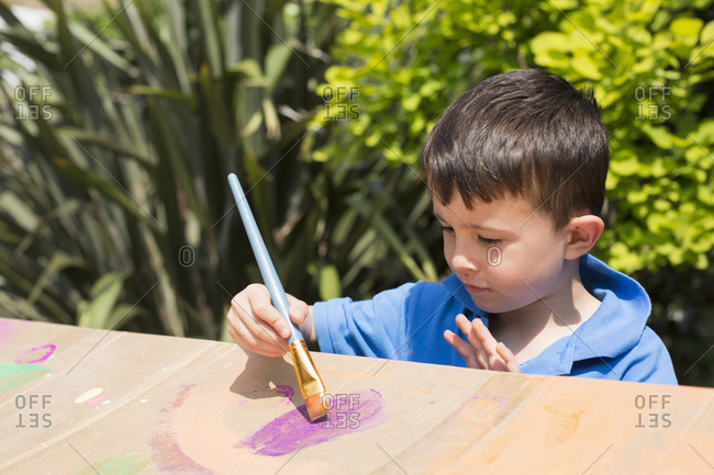 High angle view of boy painting on cardboard playhouse in back yard during sunny day