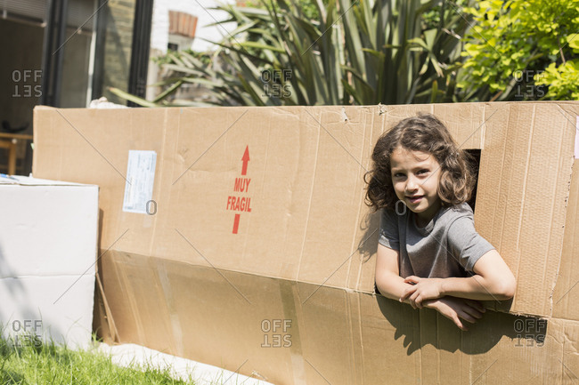 Portrait of girl in cardboard playhouse at back yard on sunny day