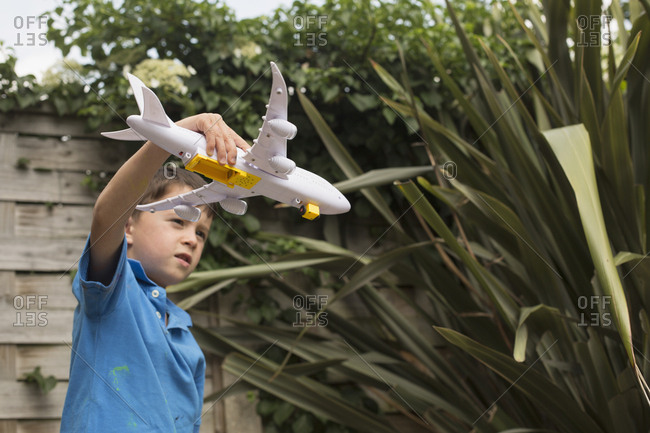 Boy playing with toy airplane against plants in back yard