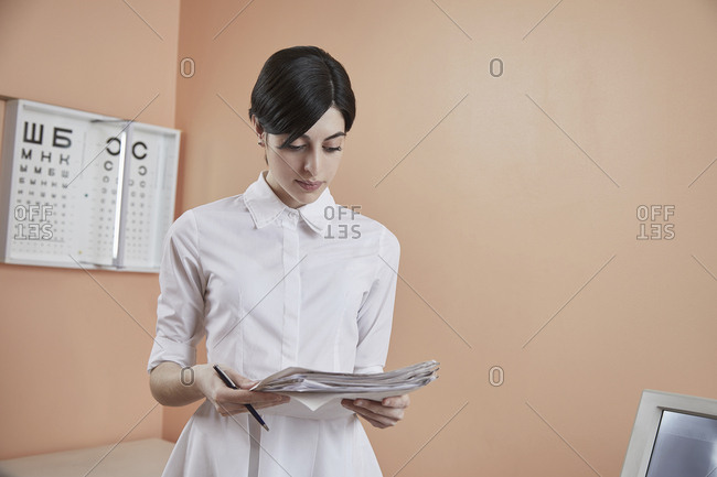 Nurse reading papers while standing in hospital
