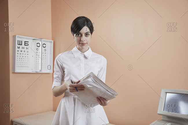 Portrait of nurse holding papers while standing in hospital