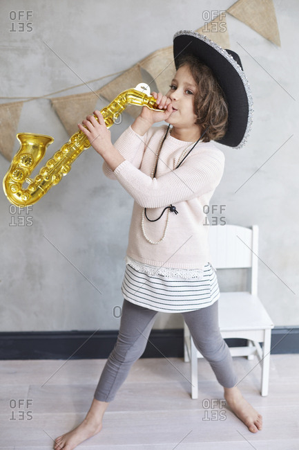 Full length of playful girl with prop trumpet standing by chair against wall