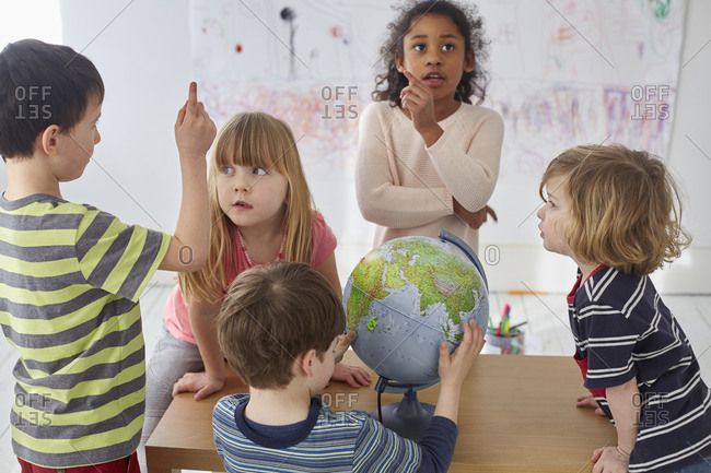 Children discussing while exploring globe at table in preschool